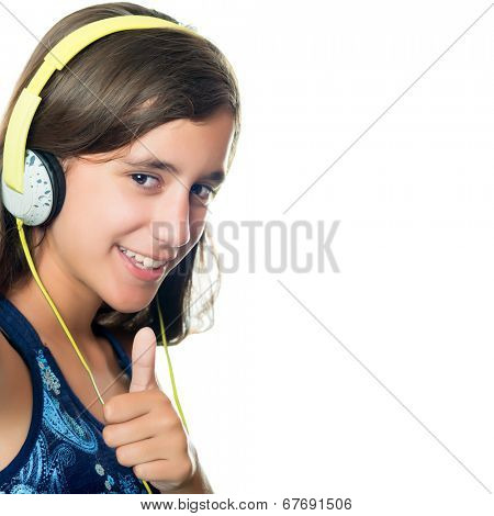 Trendy hispanic teenager listening to music on her headphones while doing a thumbs up sign isolated on white