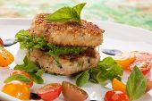 picture of crab-cakes  - Close up of crab cakes and cherry tomato salad appetizer garnished with basil and balsamic vinegar sauce - JPG