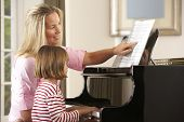 stock photo of grand piano  - Young girl playing piano in music lesson - JPG
