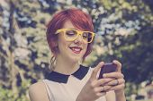 picture of toy phone  - Hipster girl text messaging on her smart phone toned image retro colors - JPG