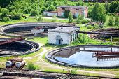 stock photo of sewage  - Round settlers at sewage treatment plant aerial view - JPG