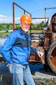 image of sewage  - Senior man mechanist standing near sewage treatment plant - JPG