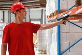stock photo of barcode  - Worker in distribution warehouse with handheld barcode scanner - JPG
