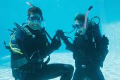 stock photo of propose  - Man proposing marriage to his shocked girlfriend underwater in scuba gear on their holidays - JPG