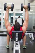 foto of work bench  - Bodybuilder lying on bench lifting dumbbells at the gym - JPG