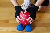 image of lifting-off  - Horizontal image of female hands wearing workout gloves while lifting red weight ball of off blue dumbbells on wooden gym floor - JPG