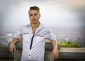 stock photo of turin  - Blond young man on top of hill above Turin Italy with city behind him - JPG