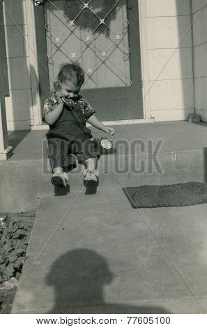 CANADA - CIRCA 1950s: An antique photo shows portrait of a little boy sitting on his doorstep.