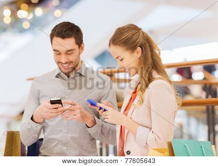 sale, consumerism, technology and people concept - happy young couple with shopping bags and smartphones in mall