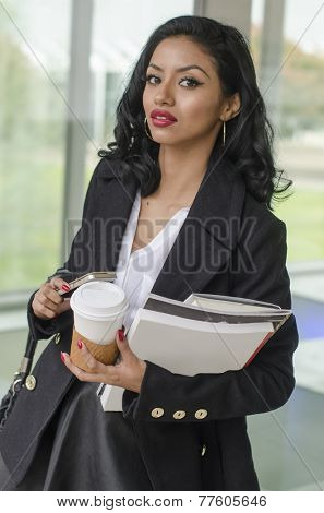 Lifestyle of attractive professional young woman busy walking - holding books,coffee and phone