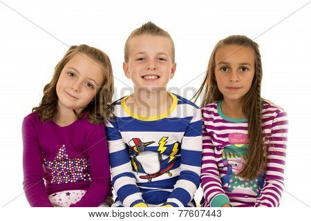 Portrait Of Three Children Wearing Colorful Winter Pajamas