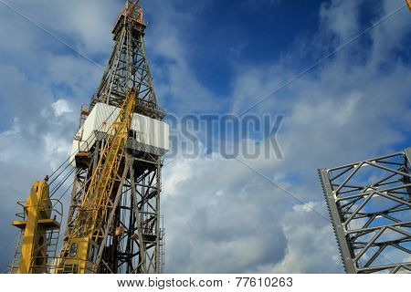 Offshore Drilling Rig With Working Cranes On Cloudy Day