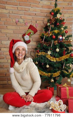 Beautiful Smiling Young Woman In Santa Hat For Christmas At Home