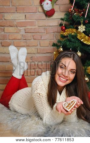 Beautiful Smiling Young Woman With Cookies Near Christmas Tree At Home