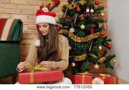 Beautiful Young Woman With Present Boxes In Santa Hat For Christmas At Home