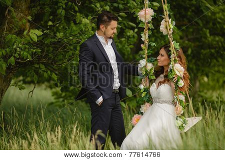 Bride and groom on a swing in the park