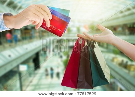 hands holding bags and credit cards