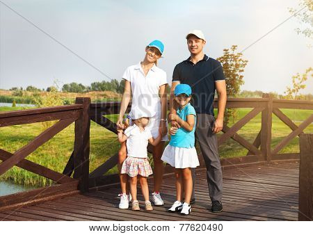 Portrait Of A Happy Young Family In Golf Club