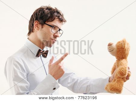 Portrait Of Serious Handsome Man Scolding Teddy Bear