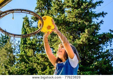 Seven year old girl  playing basketball