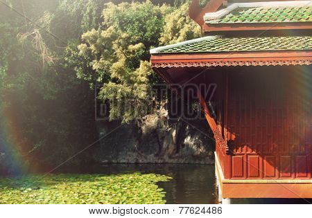 Beautiful Nature Background Of Traditional Chinese House On The Lake With Koi Fish In Sunny Beam