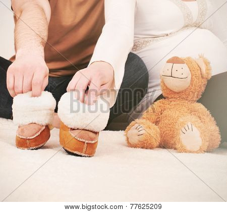 Hands Of Pregnant Couple With Little Boots For Baby