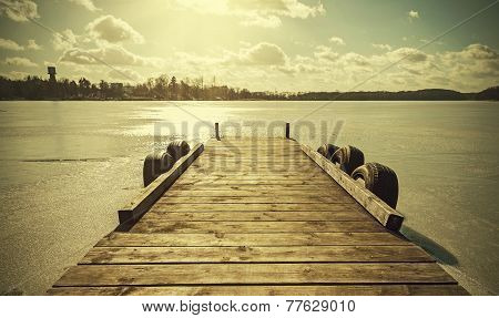 Vintage Retro Toned Image Of A Pier On Frozen Lake.
