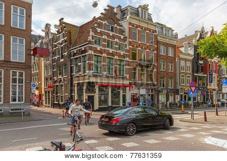 Cyclists And Car On A Typical Intersection In Amsterdam