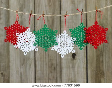 Christmas snowflakes hanging on clothesline with antique shabby wooden background
