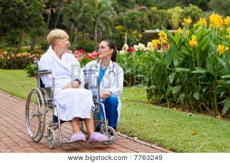 young nurse talking to wheelchair patient