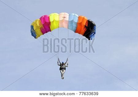 The Parachutist Goes Down On A Multi-colored Parachute.