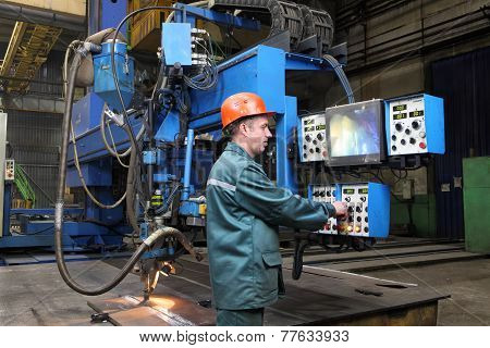 Working Operator Controls Welding Robot, Standing At Control Panel