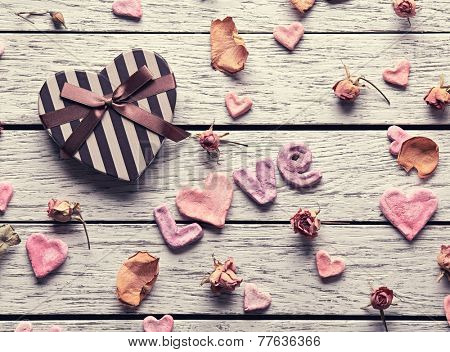 Word Love with heart shaped gift box on old white wooden plates. Sweet holiday background with petals and dried flowers.
