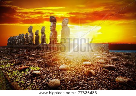 Standing Moais Against Dramatic Orange And Golden Sunset In Easter Island, Chile
