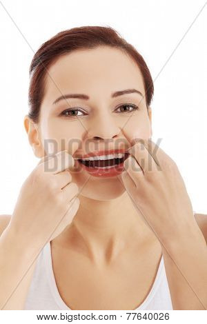 Portrait of a woman cleaning teeth with dental floss.