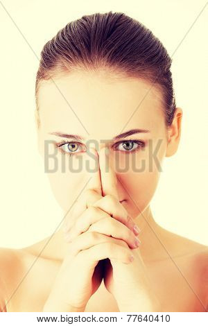 Attractive young naked woman's face. Closeup. She has fingers on her nose. Isolated on white.