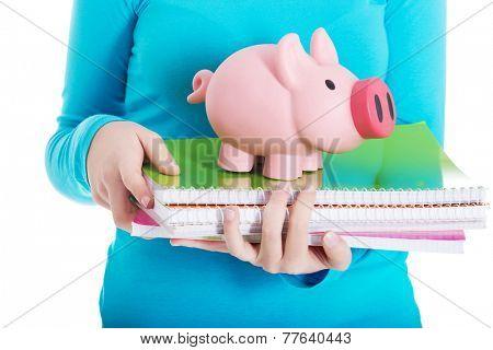 Close up on a piggybank and notebooks.
