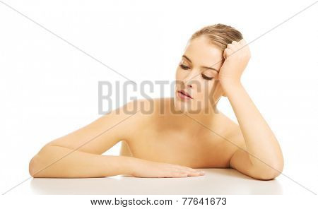 Close up of nude woman trying to take a nap at the desk.