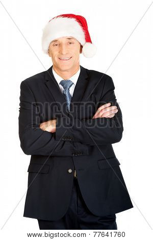 Businessman with folded arms wearing santa hat.
