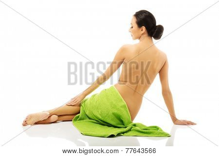 Back view of woman lying wrapped in green towel