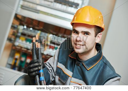electrician builder engineer worker in front of fuse switch box with cable