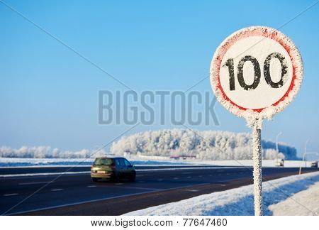Frozen speed limit sign at winter highway road