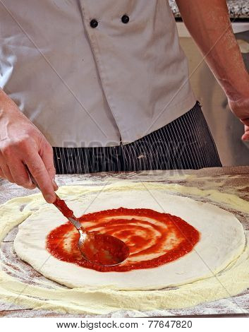 Cook adding tomato sauce on pizza dough. Cooking pizza.