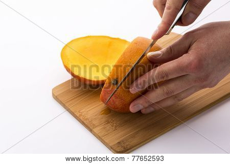Knife Positioned For A Second Cut Through A Mango
