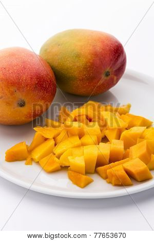 Mango Cubes And Two Whole Mangos On A White Plate