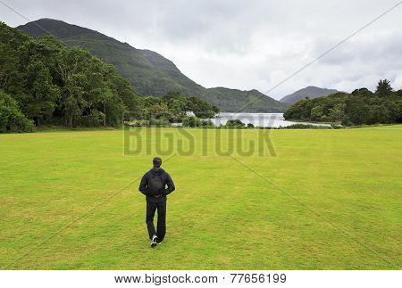 Tourist walking on lawn to the Muckross Lake.