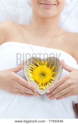 Close-up Of A Woman Holding A Bowl In The Shape Of A Heart With A Flower