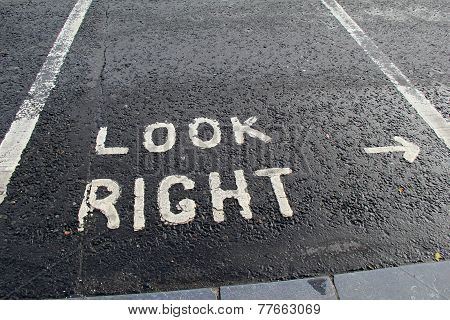 Sign on pavement that reads 'look right'