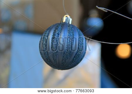 Blue holiday ornaments hanging in window