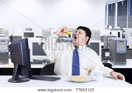 Overweight Manager Eating Junk Food